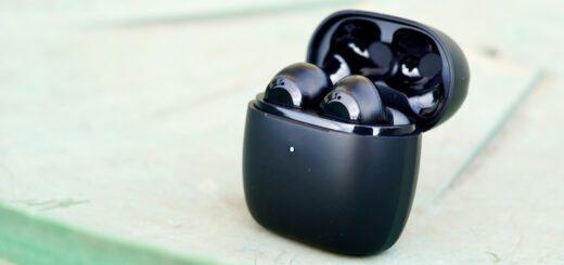 EarFun Air Kopfhoerer steht auf gruenem Tisch mit geoeffnetem Deckel 1 520x245