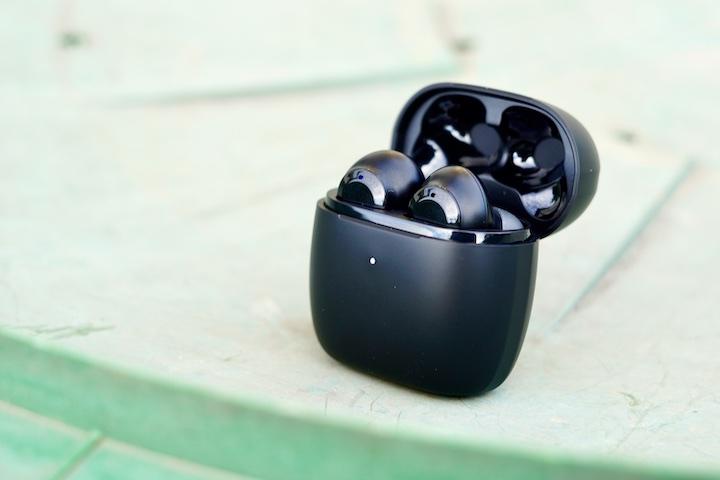 EarFun Air Kopfhoerer steht auf gruenem Tisch mit geoeffnetem Deckel 1