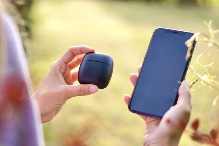Frau haelt kabelloses Headset neben ein iPhone