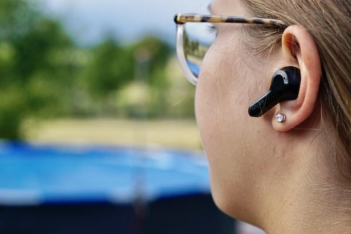 Frau mit Brille steht im Freien und hoert Musik mit einem Ohrstoepsel