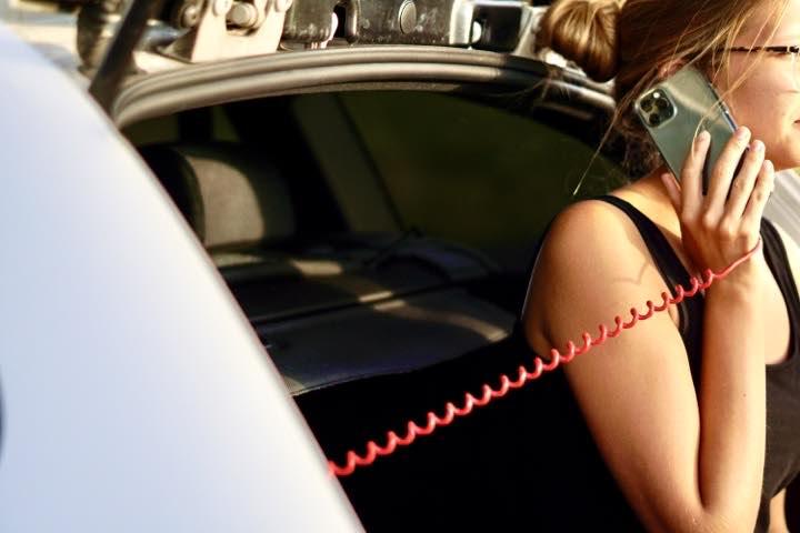 Frau telefoniert mit einem iPhone an einem Ladekabel