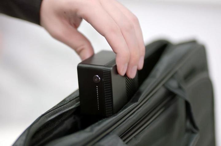 Hand steckt Mini Computer in eine Tasche
