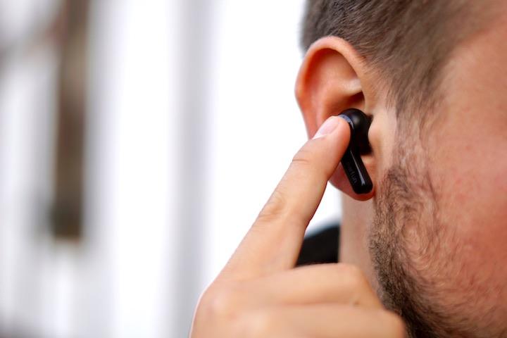 Mann tippt mit seinem Finger auf einen Ohrstoepsel