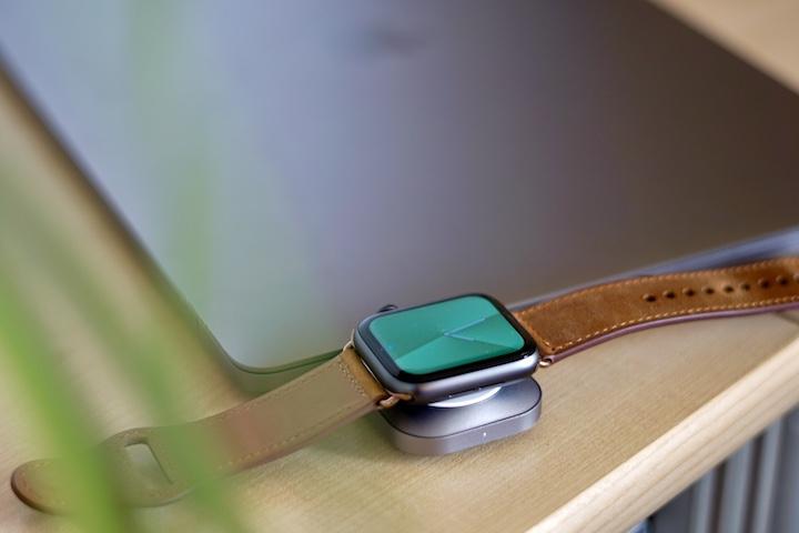 Smartwatch wird an einem zugeklappten Laptop geladen