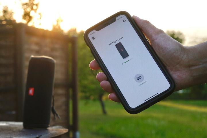JBL Connect App auf iPhone vor einem kabellosen Lautsprecher in der Sonne