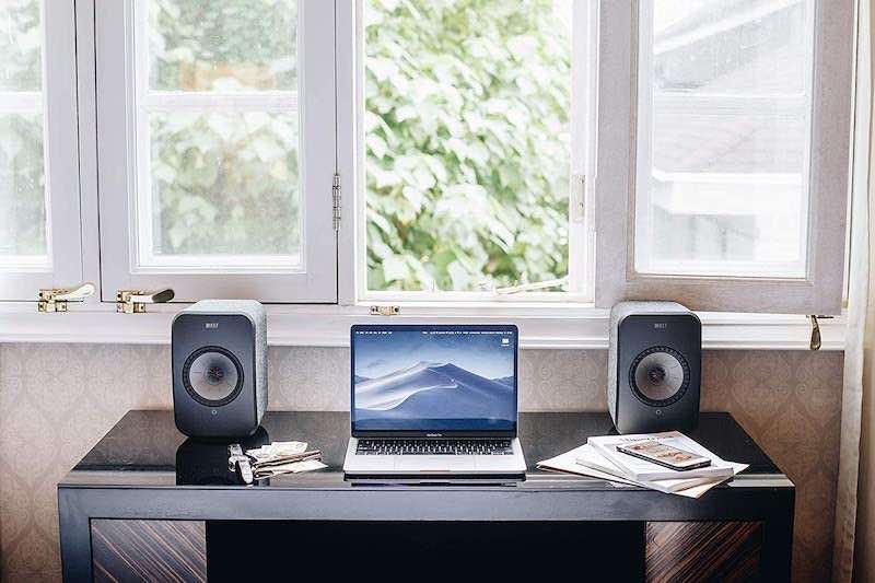 KEF LSX WLAN Lautsprecher auf Schreibtisch neben MacBook