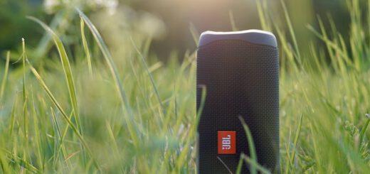 Kabelloser Bluetooth Lautsprecher steht im gruenen Gras bei Sonnenschein 520x245