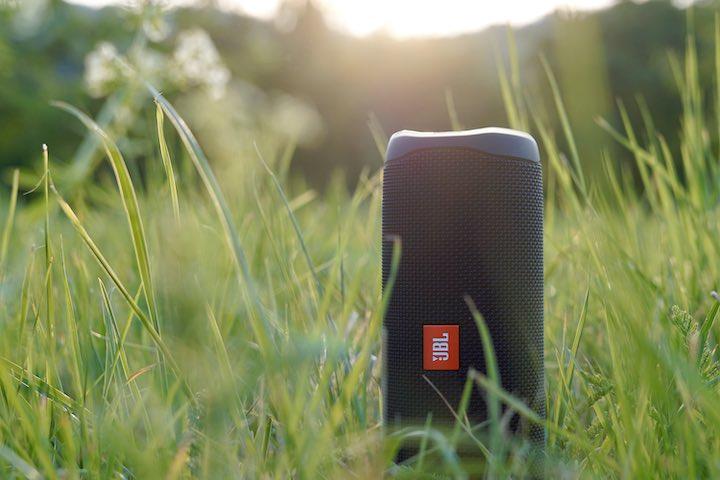 Kabelloser Bluetooth Lautsprecher steht im gruenen Gras bei Sonnenschein
