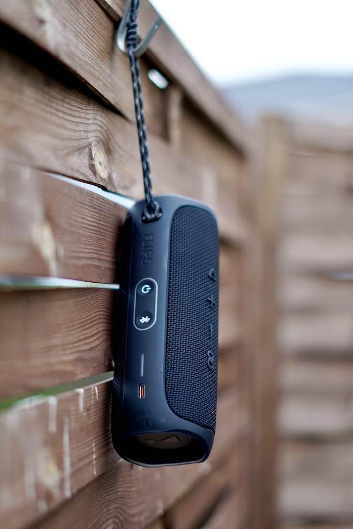 Schwarzer Lautsprecher ist an einer Holzwand befestigt