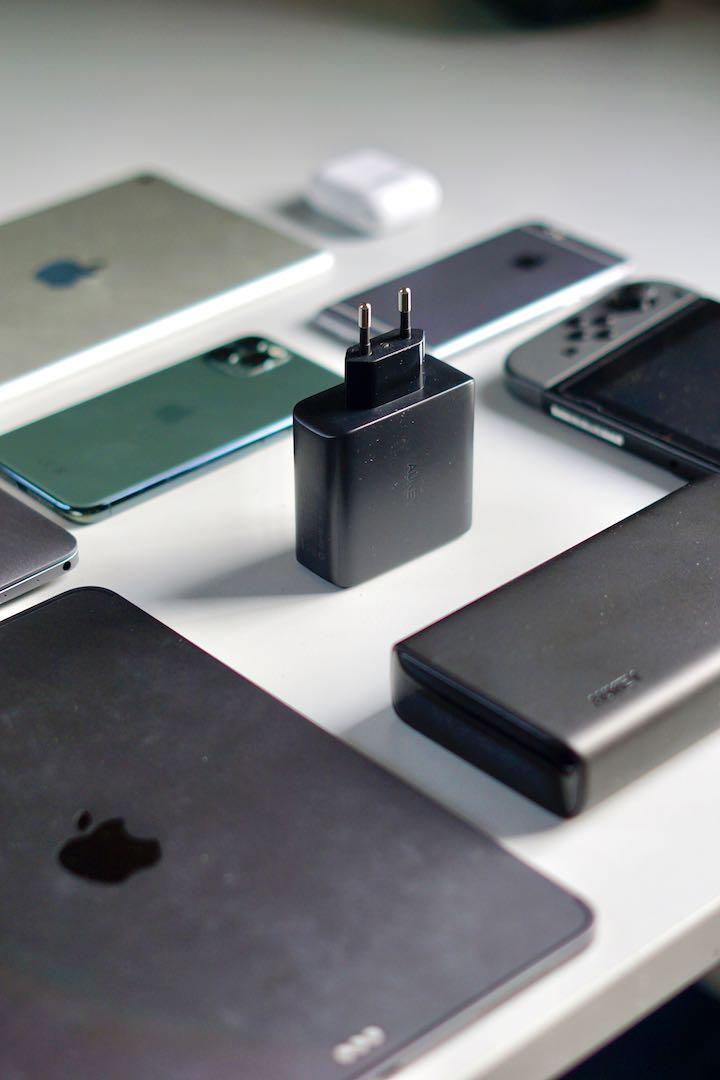 Aukey 60W Wandladegeraet steht neben iPad MacBook und iPhone