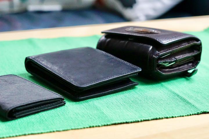 Drei Geldbeutel liegen auf gruenem Stoff nebeneinander