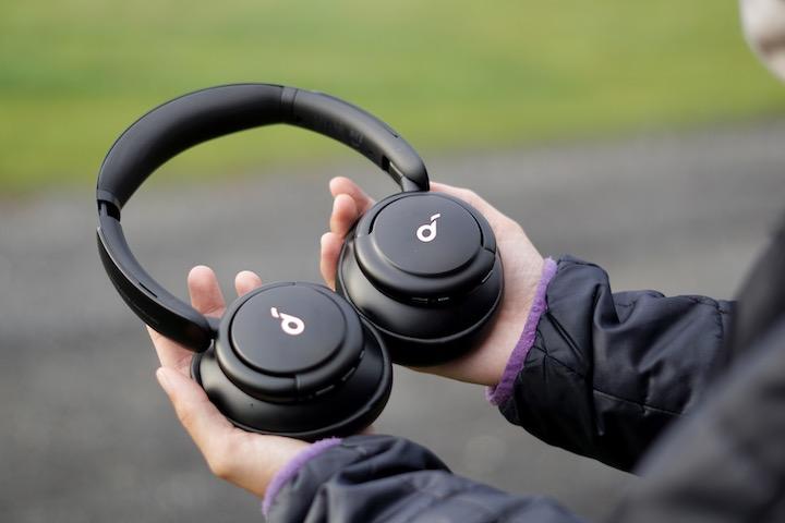Haende halten Bluetooth Kopfhoerer fest