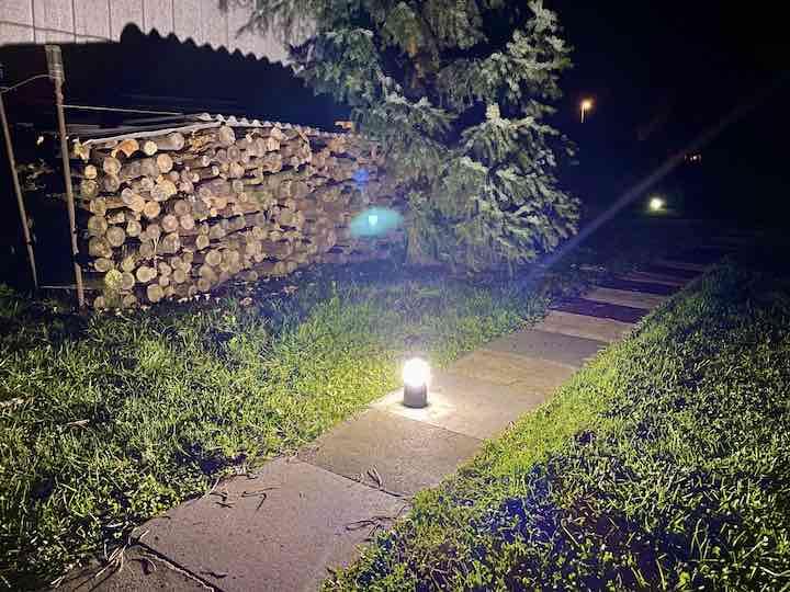 Helles Licht steht auf einer Wiese vor Holz