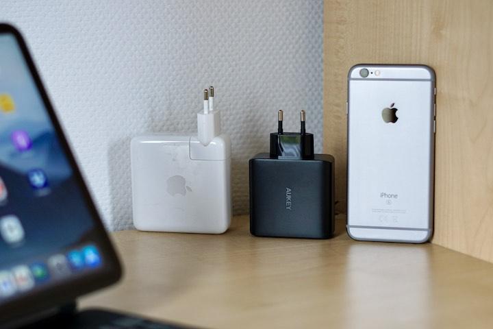 MacBook Ladegeraet steht neben einem Netzteil und iPhone