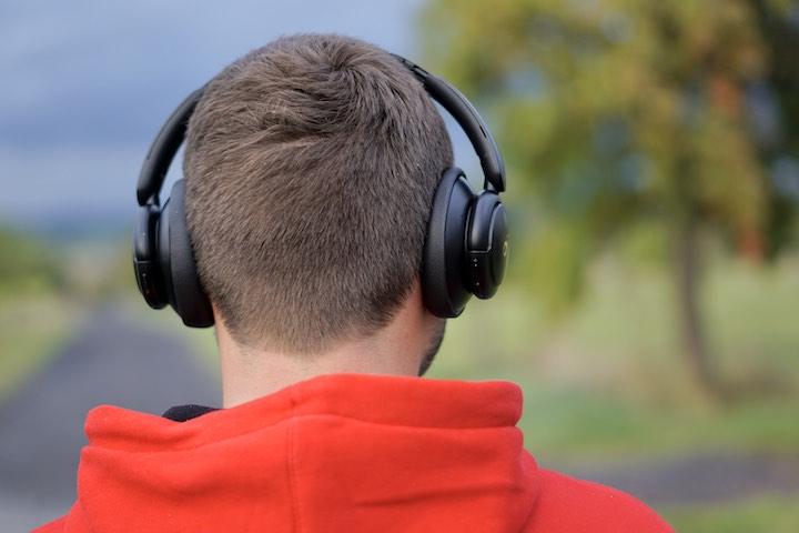 Mann hat Bluetooth Kopfhoerer auf dem Kopf