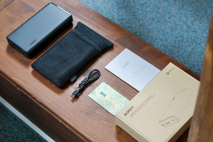 Mobiler Akku liegt neben einem Zettel und einem Karton auf Holz