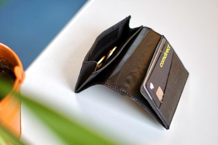 Slim Wallet mit Karten und Geld liegt neben einer Pflanze auf einem Tisch