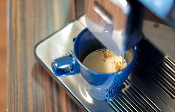 Blaue Tasse mit Kaffee wird gerade gefuellt