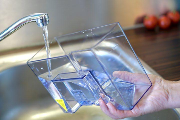 Hand haelt Wassertank fest der gerade befuellt wird