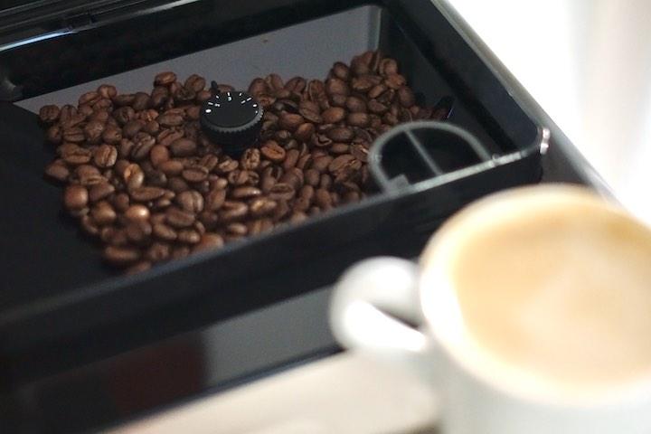 Kaffeebohnen liegen vor einem Kaffee