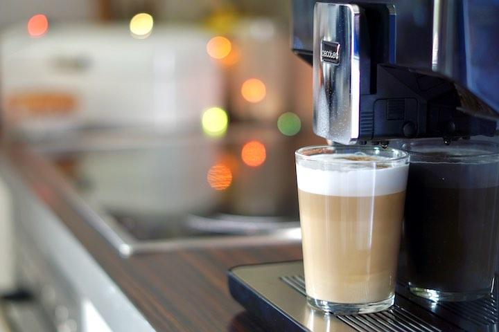 Latte Machiatto auf einer Kaffeemaschine mit Bokeh im Hintergrund