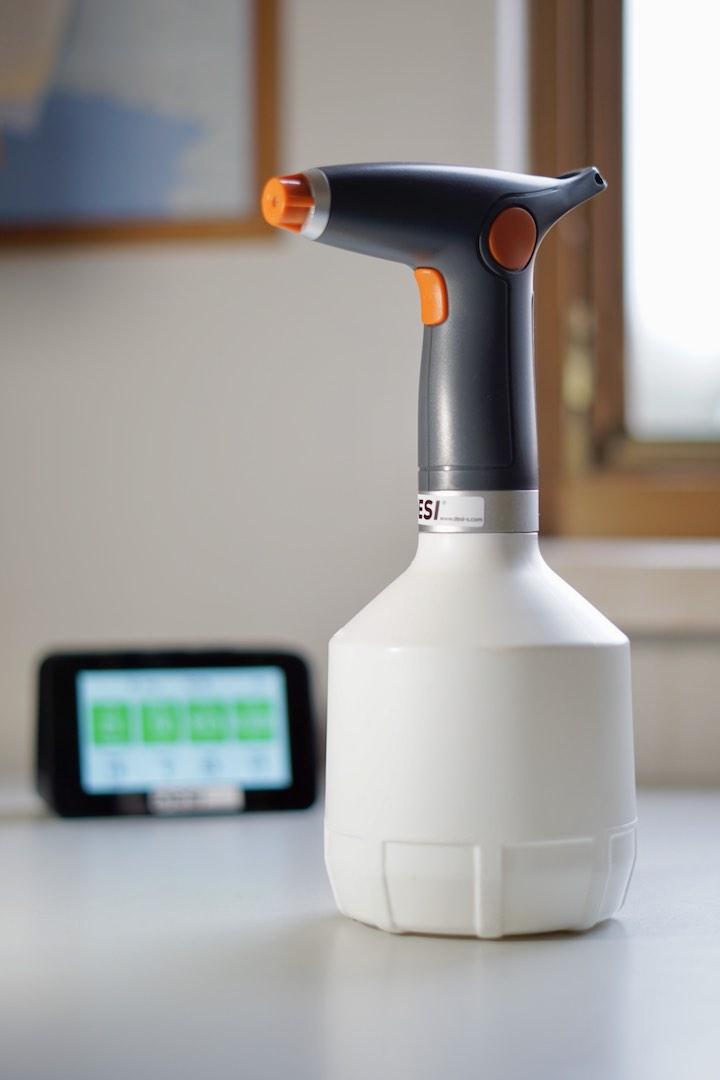 Spruehflasche steht neben Bildschirm auf einem Tisch