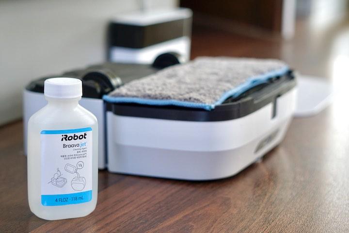 Waschmittel Laesung steht vor einem Roboter von iRobot