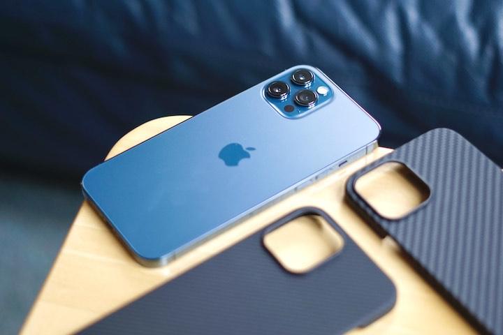 iPhone 12 Pro Max in blau liegt auf einem Tisch neben zwei Huellen