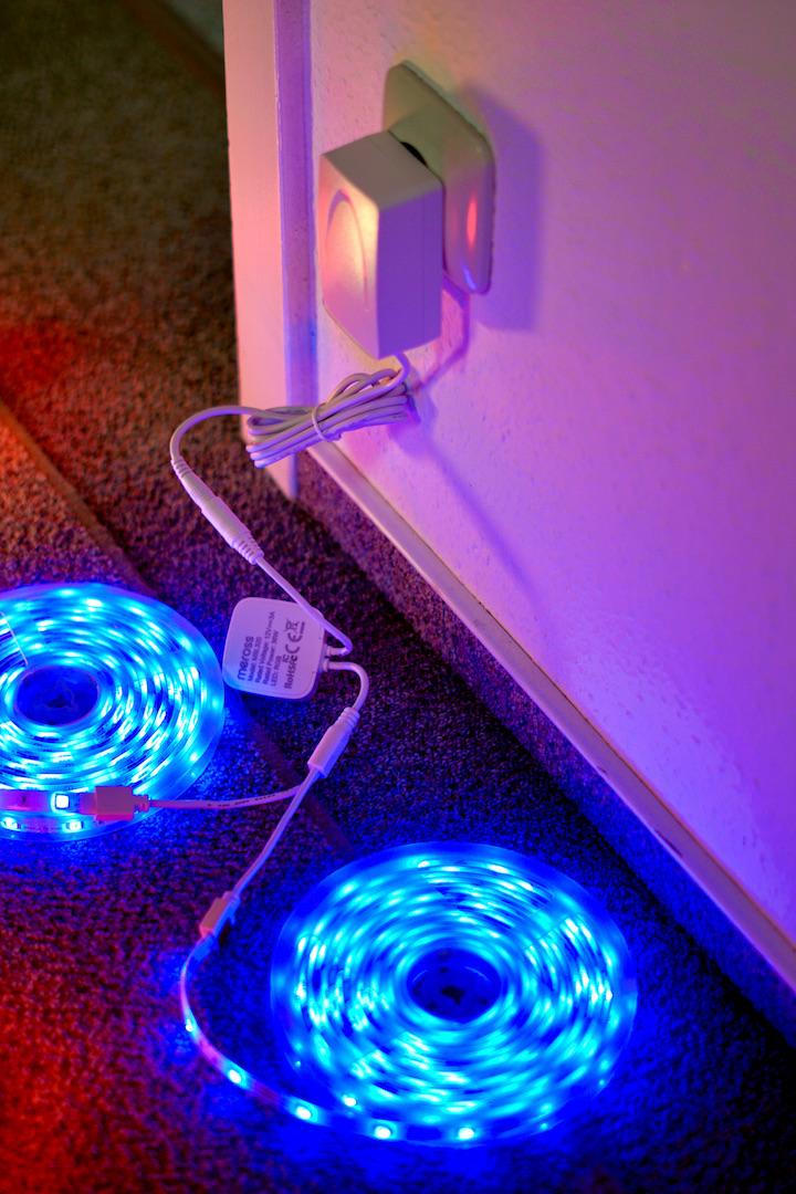 Blauer LED Smart Strip liegt bei einer Steckdose