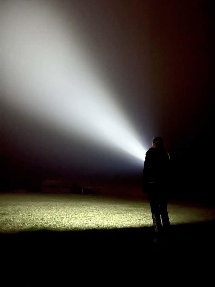 Frau leuchtet nachts in den Himmel