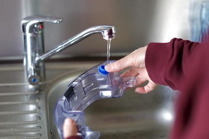Haende halten Wassertank fest der gerade gefuellt wird