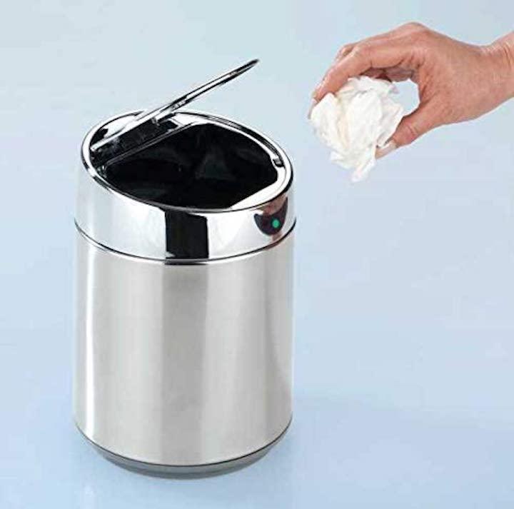 Hand wirft Abfall in Eimer mit Sensor