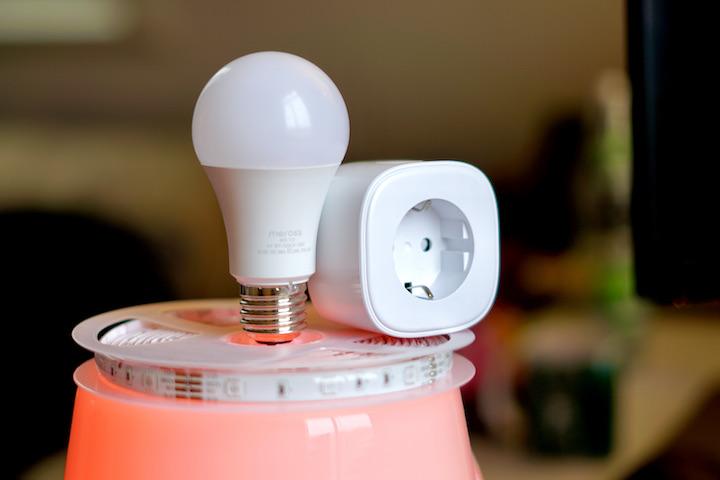 Meross Smart Plug und Gluehbirne liegen auf einem LED Streifen