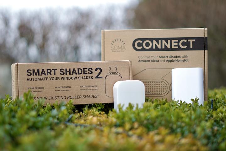 SOMA Smart Shades 2 und Connect Box liegen auf einem gruenen Busch