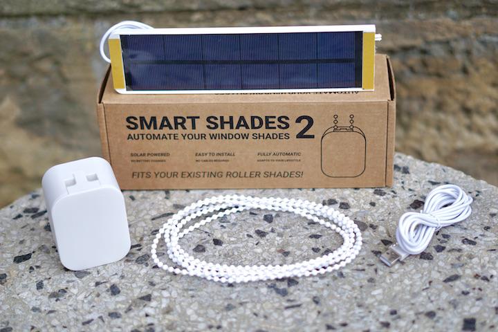 Smart Shades 2 Lieferumfang liegt mit Kabel uns Solarpanel auf einer Steinplatte