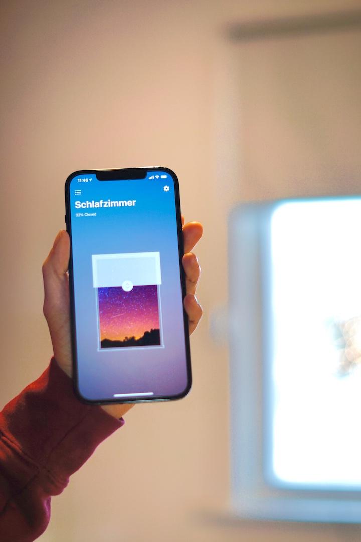 Smart Shades App auf einem iPhone mit Fenster im Hintergrund