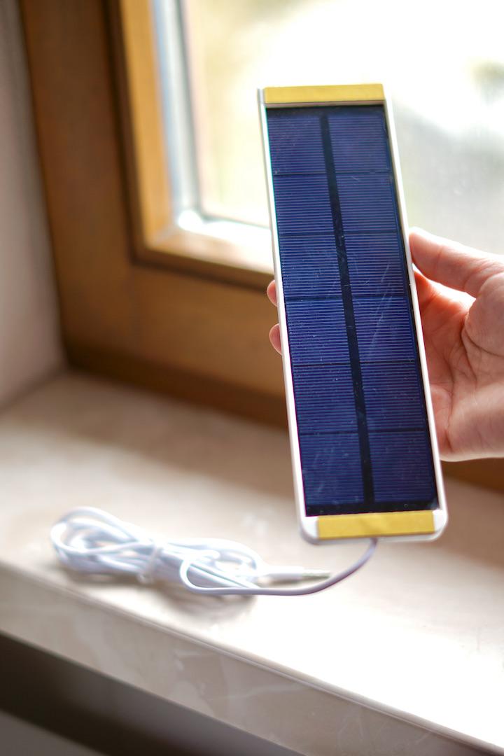 Solarpanel wird vor ein Fenster gehalten