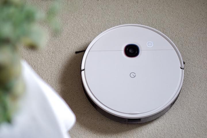 Yeedi 2 Hybrid Saugroboter mit Wischfunktion steht neben einer Plfanze auf Teppichboden
