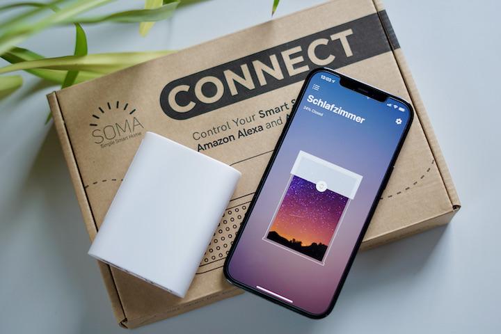iPhone und SOMA Connect Box liegen neben einer Pflanze auf einem Karton