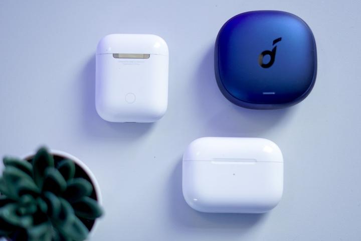 AirPods AirPods Pro und Soundcore Bluetooth Headset Cases liegen auf einem Tisch