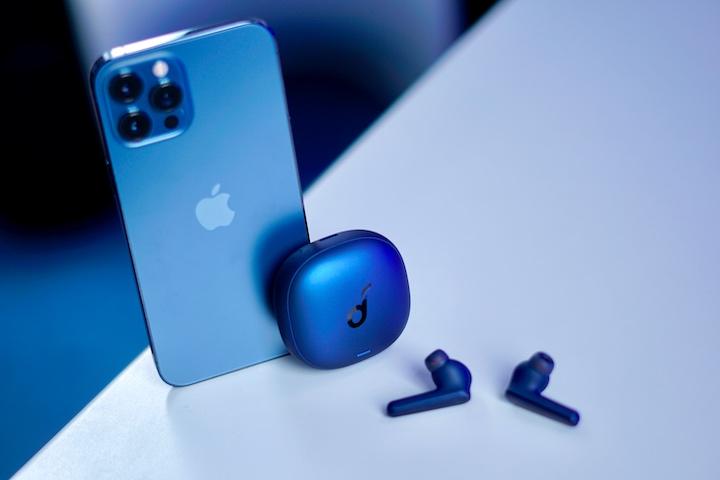 Blaues iPhone 12 Pro Max und blaue kabellose In Ear Kopfhoerer