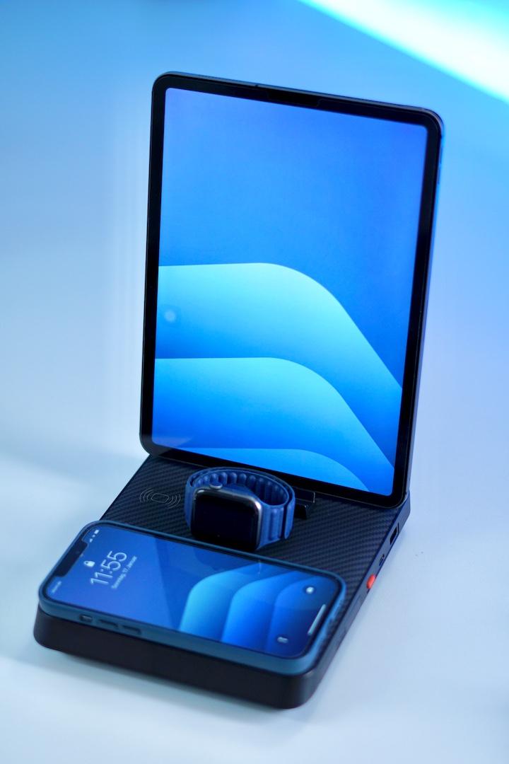 Blaues iPhone und Apple Watch stehen mit einem iPad Pro auf einer Ladestation und werden aufgeladen