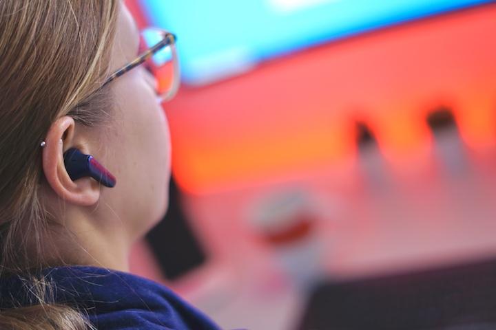 Frau sitzt vor PC und hat kabellose Kopfhoerer im Ohr