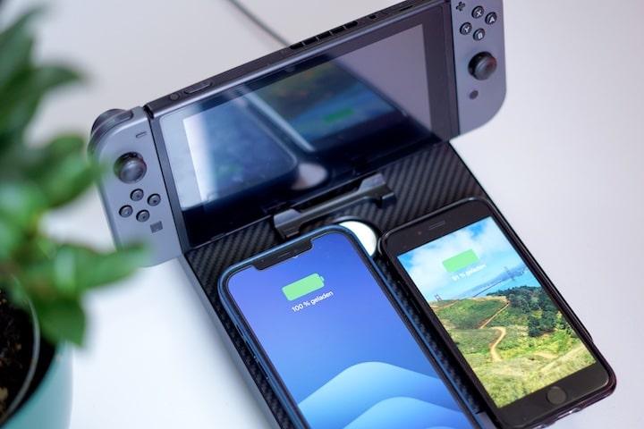 Nintendo Switch und zwei iPhones liegen auf einer Ladestation