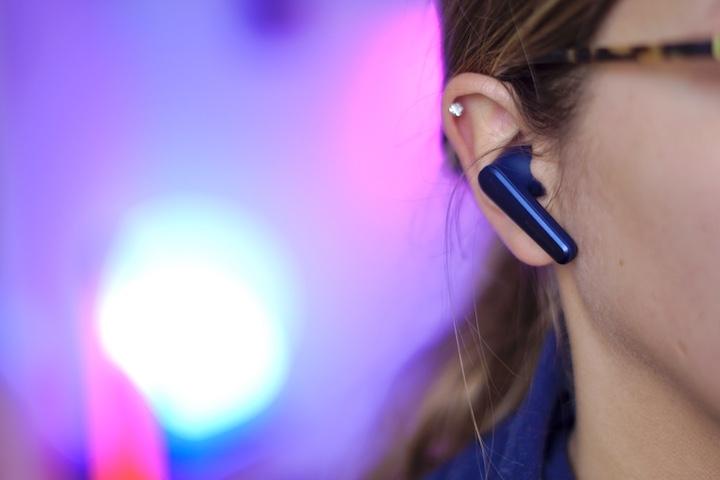Soundcore Liberty Air 2 Pro Headset in einem Ohr vor buntem Hintergrund
