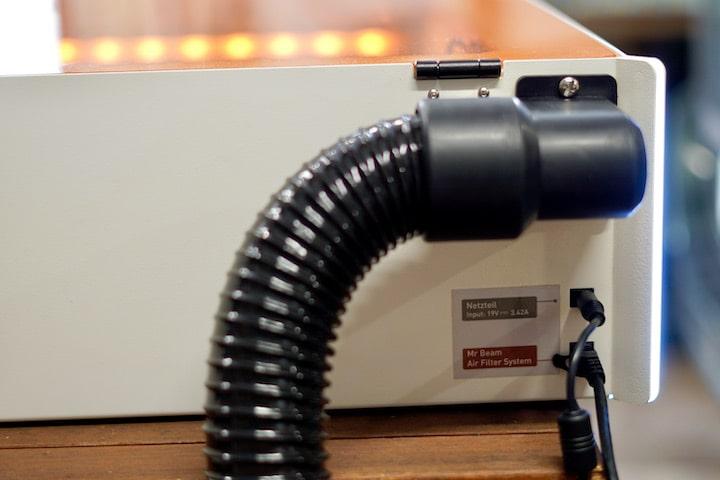 Abgasschlauch und LAN Kabel stecken in einem Lasercutter