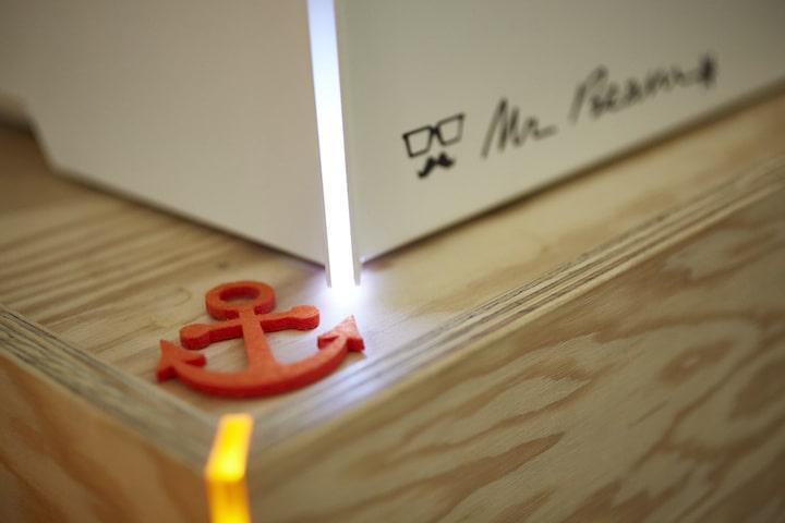 Anker aus orangem Filz liegt auf einer Holzplatte