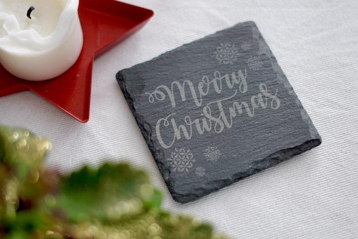 Frohe Weihnachten Merry Christmas Untersetzer liegt neben einer Kerze