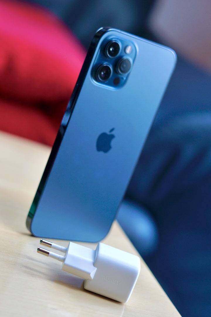 Kompakter Netzstecker liegt vor einem blauen iPhoen 12 Pro Max