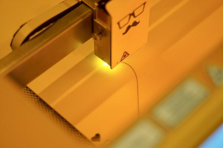 Laser graviert eine Holzplatte